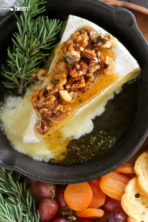 Baked brie cheese topped with honey and walnuts in a cast iron skillet.
