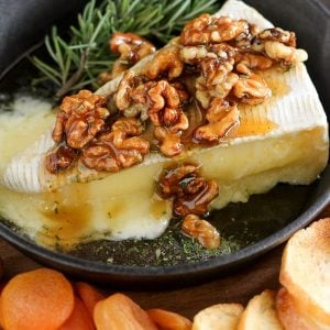 Wedge of brie cheese topped with walnuts and honey.