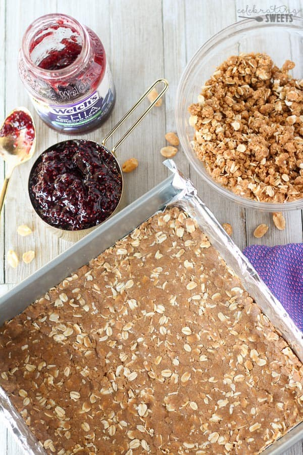 Healthier Peanut Butter and Jelly Crumble Bars - The classic flavors of peanut butter and jelly combine in these healthier crumble bars. A whole-grain brown sugar oat crust, Welch's Chia Concord Grape Fruit Spread and a sweet and salty peanut crumble. Enjoy for breakfast, snack or dessert.