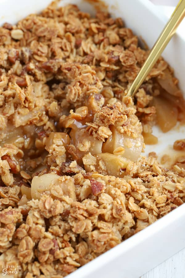 Healthy Apple crisp in a white casserole dish with a gold spoon
