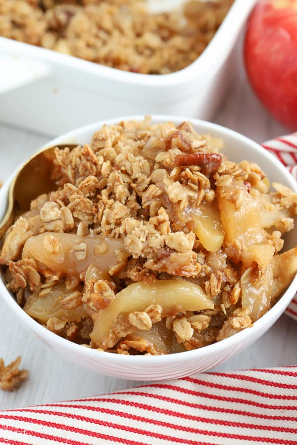 Apple crisp in a white bowl next to a red and white striped napkin
