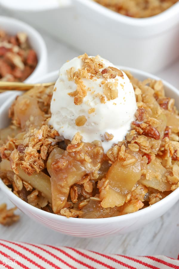 Apple crisp in a white bowl topped with ice cream