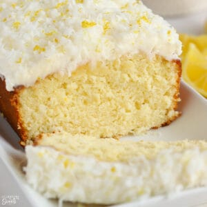 Lemon coconut cake topped with frosting and shredded coconut