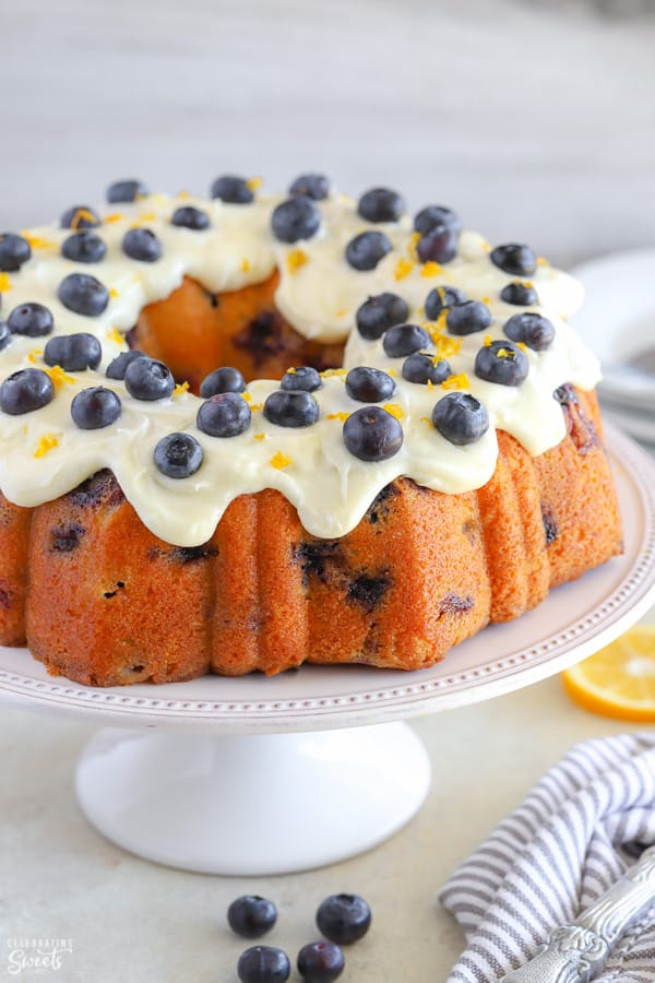 Lemon blueberry bundt cake topped with cream cheese frosting and fresh blueberries.