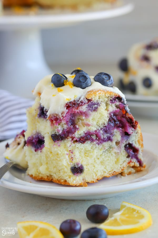 Slice of lemon blueberry cake on a white plate.