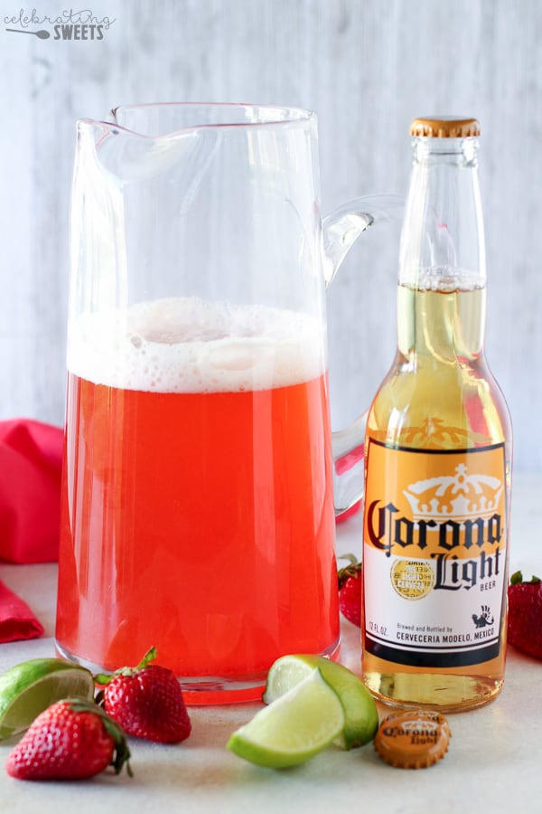 Strawberry Lime Shandy in a Pitcher with a Bottle of Beer next to it.