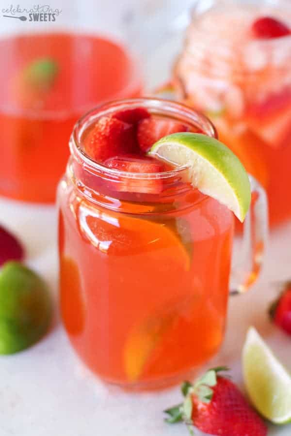 Strawberry Lime Shandy in a Glass with Strawberries and a Lime Wedge.