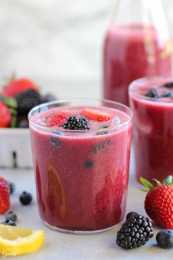 Glass of berry agua fresca topped with fresh berries.