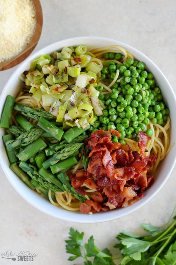 Creamy pasta with bacon, peas, asparagus, and leeks tossed in a light alfredo sauce. You'll love this Spring Vegetable and Bacon Alfredo Pasta!