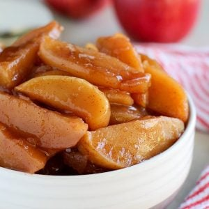 White bowl filled with sliced cinnamon apples