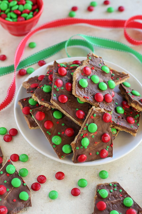 Christmas bark with red and green M&M's on a white plate with red and green ribbon in the background.
