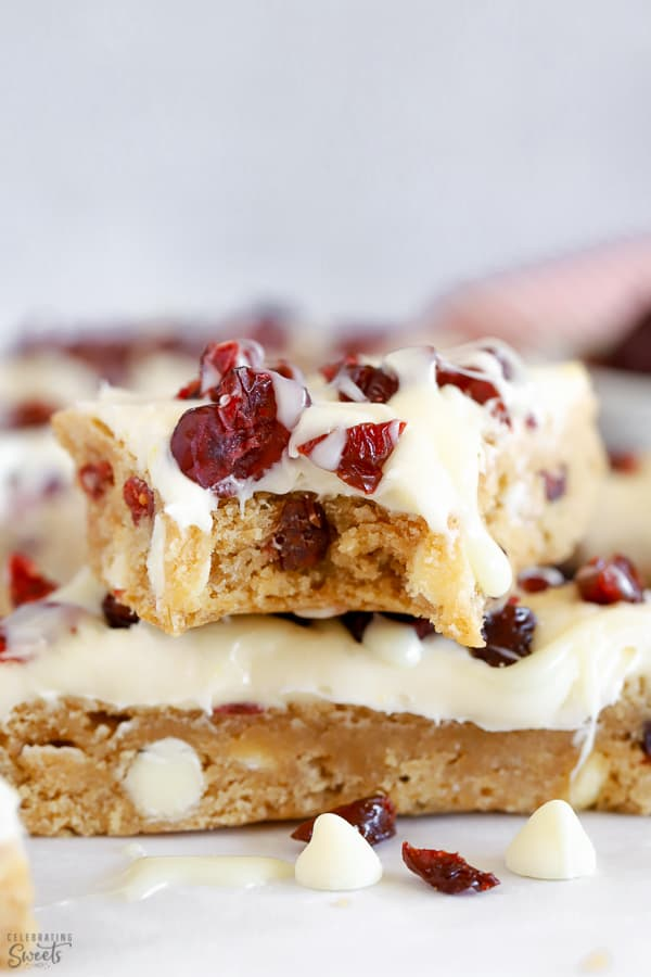 Two blondies topped with frosting and dried cranberries.