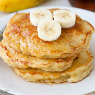 Stack of three banana pancakes on a white plate.