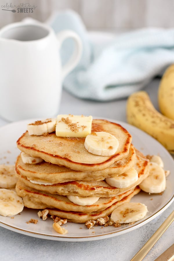 Stack of Banana Pancakes topped with butter, sliced bananas and brown sugar.