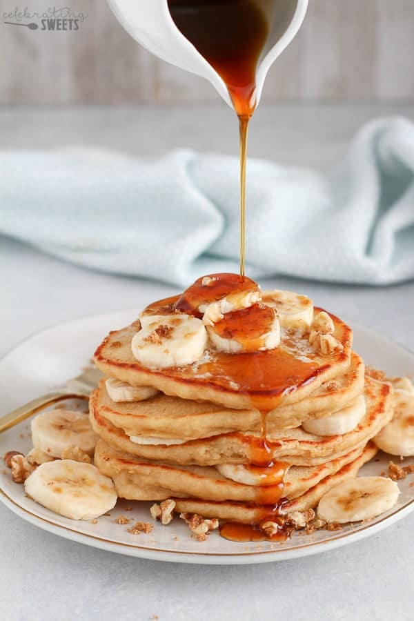 Stack of pancakes with maple syrup being poured over the top.