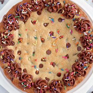 Giant chocolate chip cookie decorated with chocolate frosting and sprinkles.