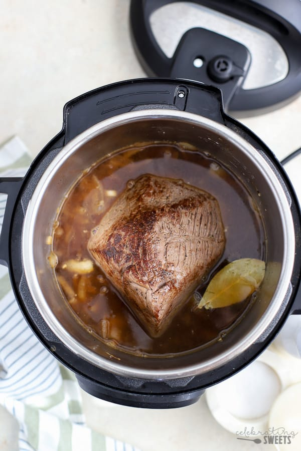 Instant pot with a beef roast in it.
