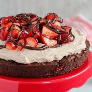 Large brownie topped with whipped cream and strawberries.