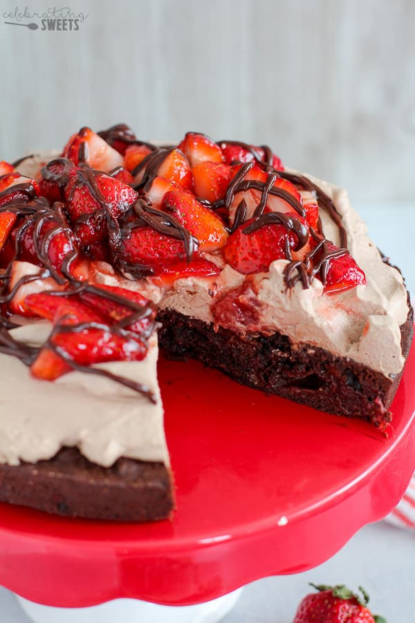 Brownie pie topped with whipped cream and strawberries.