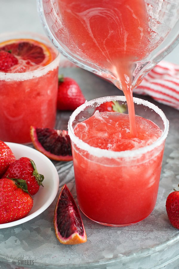 STrawberry margarita being poured into a glass.