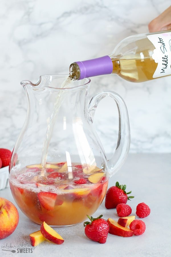 Wine poured into a pitcher for peach sangria.