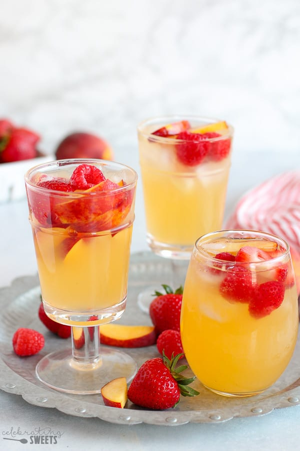 Three glasses of peach sangria on a tray.
