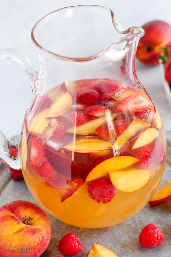 Peach Sangria in a glass pitcher.
