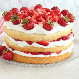 Three layers of cake filled with whipped cream and strawberries on a glass plate.