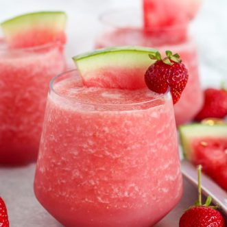 Pink wine slushie garnished with watermelon and strawberry.