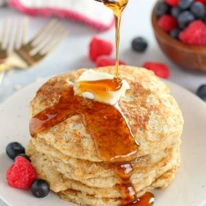 Syrup being poured over a stack of pancakes.