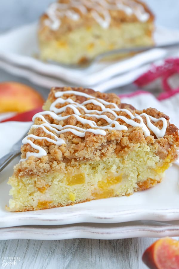 A slice of Peach Crumb Cake on a white plate.