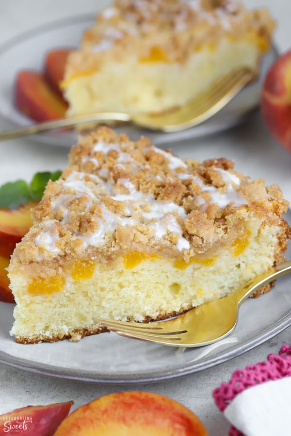 A slice of Peach Crumb Cake on a grey plate with a gold fork.