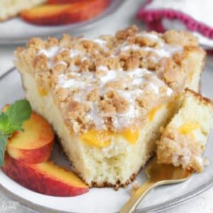 A slice of Peach Crumb Cake on a grey plate with peach slices.