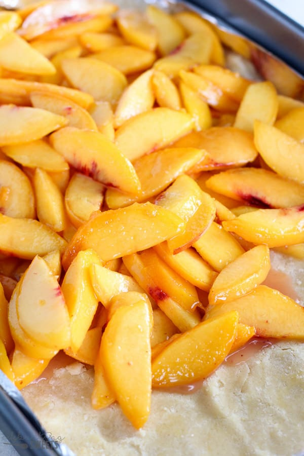 Sliced peaches on top of crust.