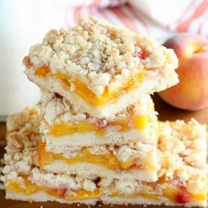 Peach crumb bars stacked on a wooden board