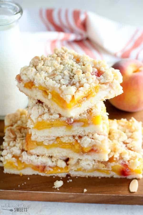 A stack of Peach Crumb Bars on a brown cutting board.