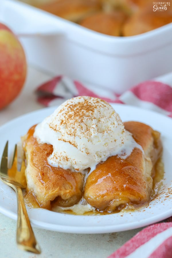 Two apple dumplings on a white plate topped with ice cream.