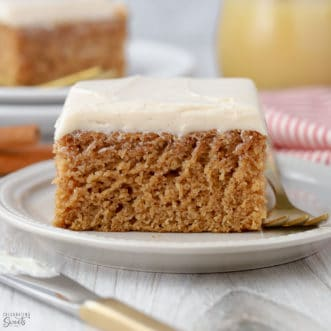 Slice of applesauce cake topped with frosting on a white plate.