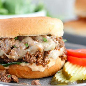 Cheeseburger Sloppy Joe on a grey plate with tomato and pickle.