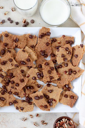 Chocolate Chip Cookie Brittle on a white plate with two glasses of milk.