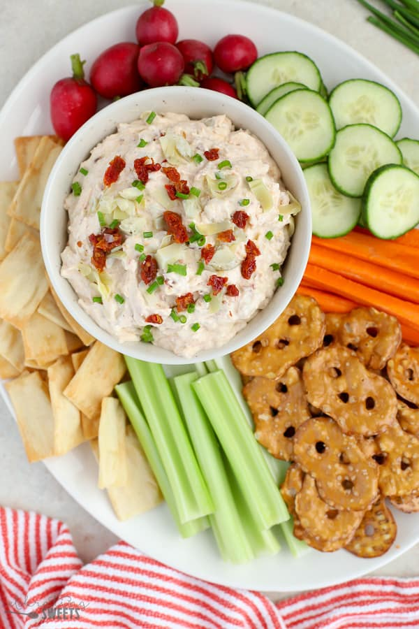 Bowl of dip topped with artichokes and sun dried tomatoes served with vegetables and pretzels.