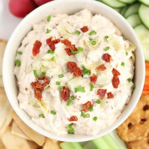 Sun dried tomato and artichoke dip in a white bowl.