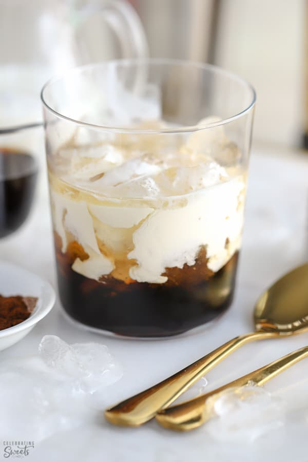 White russian cocktail in a glass with two gold spoons on the side.