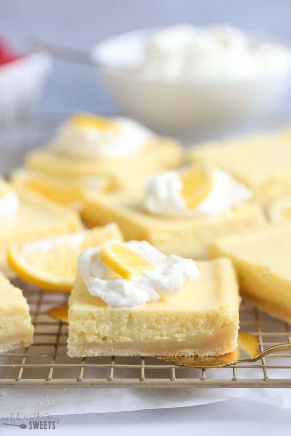 Lemon bars on a rack garnished with whipped cream and a lemon slice.