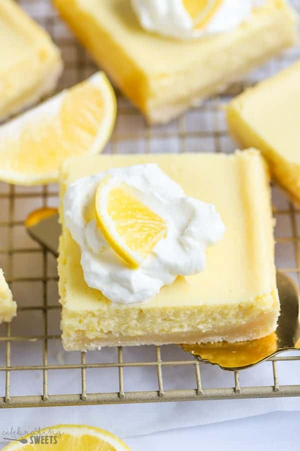Lemon Bar topped with whipped cream on a spatula.