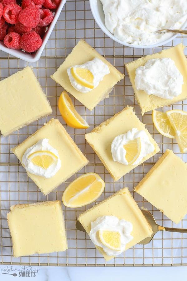 Lemon bars on a baking rack with lemon wedges.