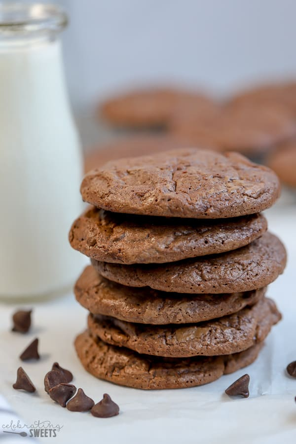Stack of brownie cookies with milk in the background.