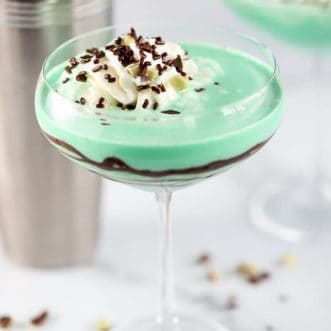Green grasshopper drink in a stemmed glass with swirled with chocolate syrup.