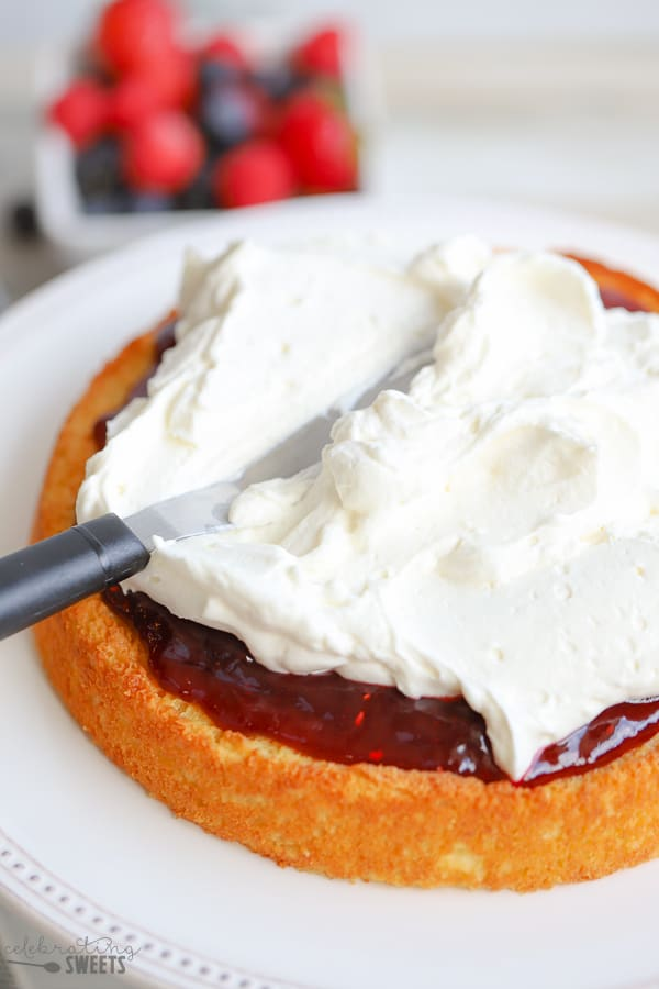 Cake topped with jam being spread with whipped cream.