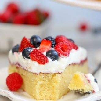 A slice of cake topped with whipped cream and mixed berries.